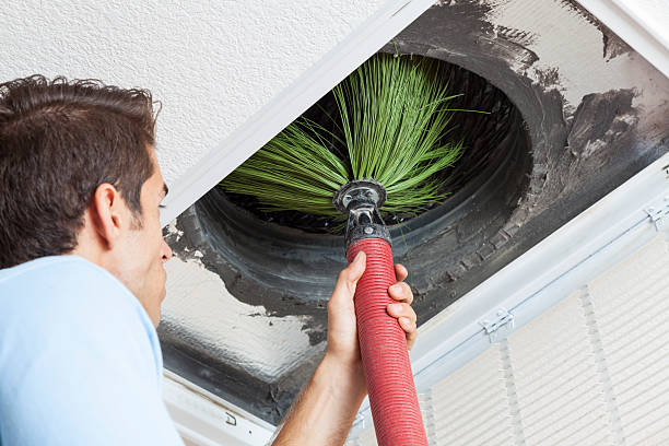 He is getting the dust out of the air ducts so that the air quality is better and doesn't cause any health prolems